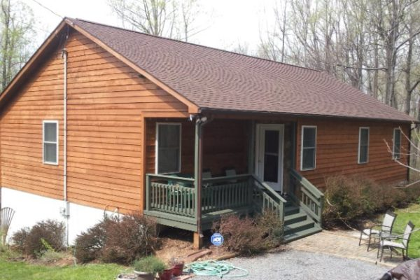 Home with wood siding and brown roof