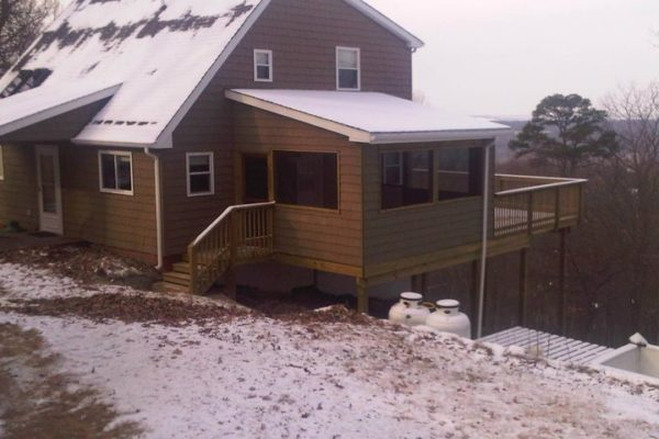 Shingled house with screen porch and deck with dusting of snow